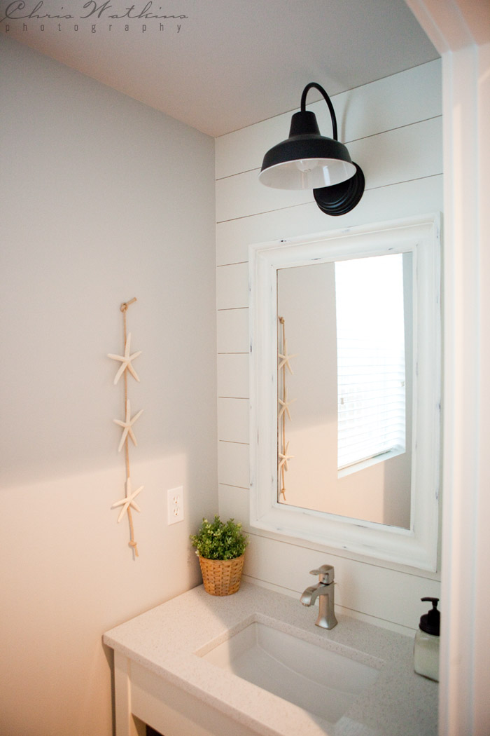 Barn wall sconce lends farmhouse look to powder room for Light fixtures for bathrooms